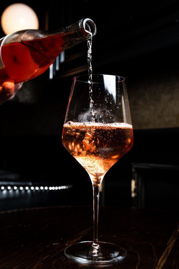 wino różowe kieliszek na ciemnym tle